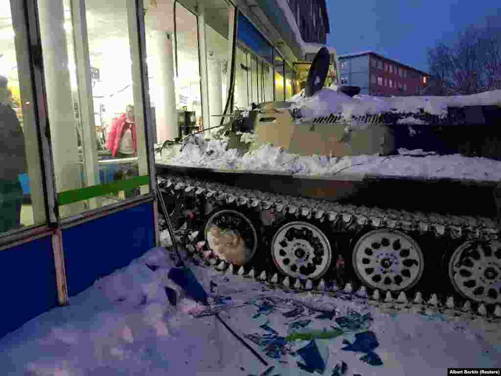 A Russian man rammed an armored personnel carrier into a shop window before he climbed through the rubble to steal a bottle of wine, in the town of Apatity. (Reuters/Albert Borkin)