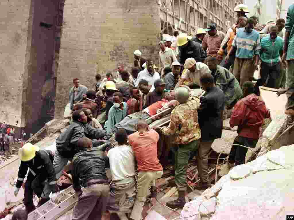 """Ратаўнікі выносяць целы людзей, забітых падчас выбуху бомбы каля амбасады ЗША ў Найробі (Кенія) у жніўні 1998. Адказнасьць узяла на сябе """"Аль-Каіда"""", загінула больш за 200 чалавек"""