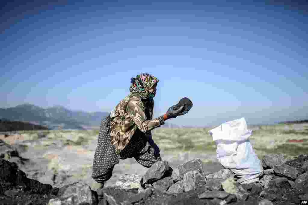 A villager collects coal outside the Soma mine in Manisa, Turkey. People gathered for the anniversary of the death of 301 workers after an explosion on May 13, 2014. (AFP/Bulent Kilic)