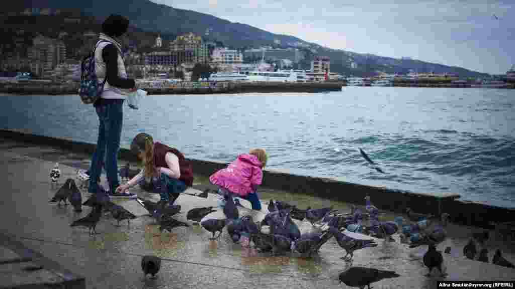 Діти годують голубів на набережній Ялти, 17 листопада 2016 року
