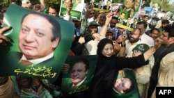 Supporters of the ruling party Pakistan Muslim League-Nawaz (PML-N) carry posters of Prime Minister Nawaz Sharif as they hold a rally after a Supreme Court verdict on the Panama Papers in Lahore on April 20.