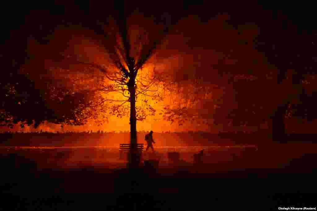 A man walks through a park during a cold, foggy night in Athboy, Ireland. (Reuters/Clodagh Kilcoyne)