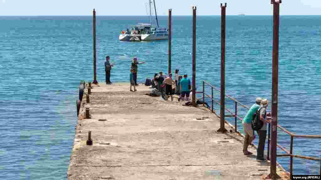 Рибалки та відпочивальники на старому пірсі під Соколом