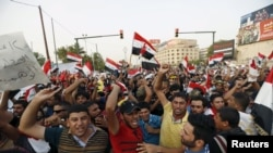 People shout slogans during a demonstration against corruption and poor services at Tahrir Square in central Baghdad on August 7.