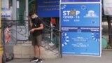 Алматыдағы аурухананың алдында тұрған адам. 2020 жылдың шілдесі.