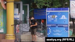 Человек в маске у входа в больницу в Алматы. Июль 2020 года.