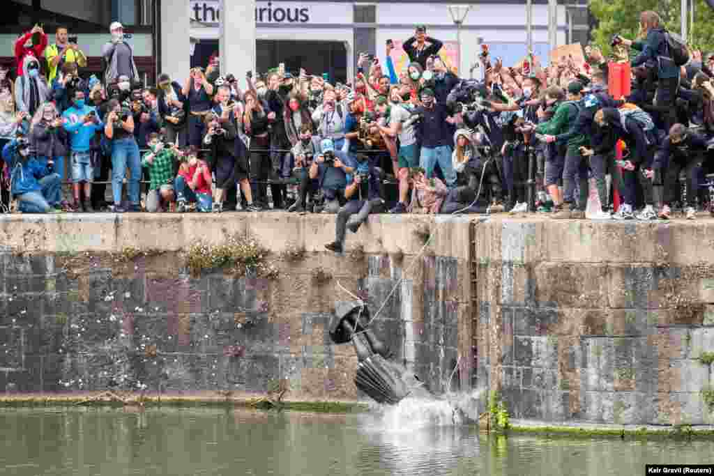 The statue of 17th century slave trader Edward Colston falls into the water after protesters pulled it down and pushed into the docks, during a protest against racial inequality in the aftermath of the death in Minneapolis police custody of George Floyd, in Bristol, Britain, June 7, 2020.