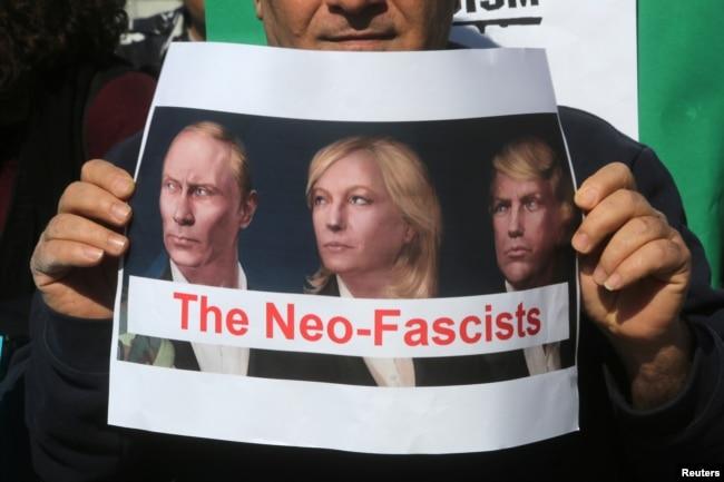 """Противник Марин Ле Пен держит плакат с изображением Ле Пен, Владимира Путина и Дональда Трампа и надписью """"Неофашисты"""""""