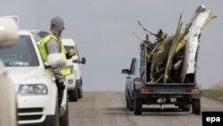 Експерт дивиться на автомобіль, що транспортує уламки «Боїнга» в Донецькій області, 16 квітня 2015 року
