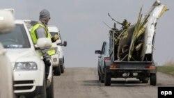 Участник следственной группы смотрит на автомобиль, в котором перевозят обломок самолета в Донецкой области, 16 апреля 2015