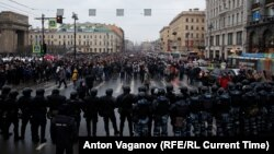 Russian law enforcement officers block a road as protesters march during a rally in support of jailed Russian opposition leader Alexei Navalny in St. Petersburg on January 23.