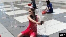 """Anëtaret e grupit """"Haveit"""" duke performuar në fontanat në sheshin e Prishtinës shenjë proteste për reduktimet e ujit."""