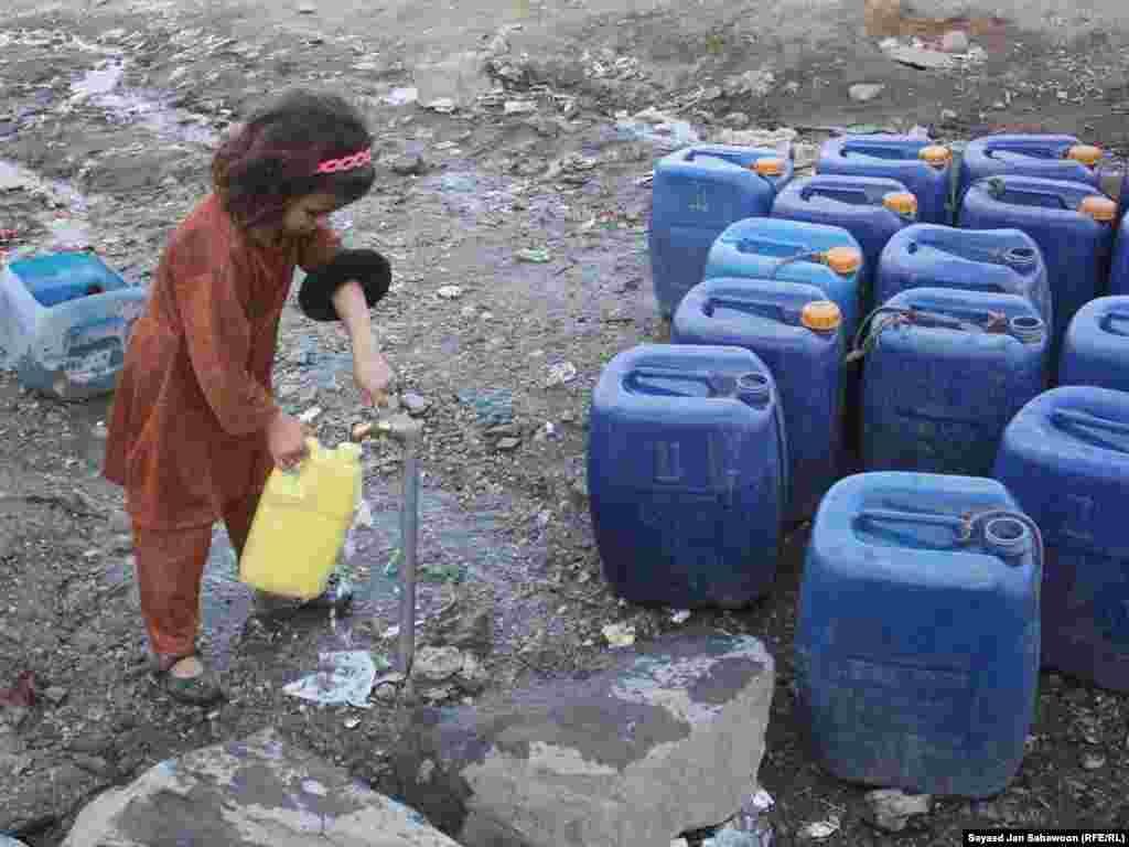 An Afghan girl fills cans from a community tap in Kabul.