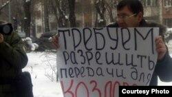 """Активист незарегистрированной оппозиционной партии """"Алга"""" Ерлан Калиев проводит одиночный пикет у здания ДКНБ. Алматы, 16 февраля 2012 года."""