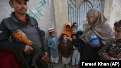 FILE: A police officer stands guard while a health worker gives polio vaccine to a girl in southern Pakistani city of Karachi.