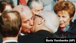 Mihail Gorbaciov îl îmbrățișează pe liderul est-german Erich Honecker la sosirea pe aeroportul Schoenefeld în Berlinul de răsărit pe 6 octombrie 1989. (AP-Photo/Boris Yurchenko)