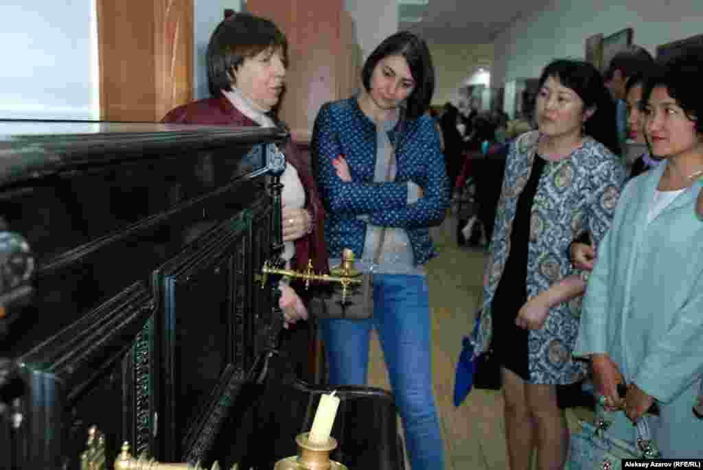 Следующим на пути был Музей истории города Алматы. Он находится в довольно тесном помещении на первом этаже здания, известного в народе как «Три богатыря». Из-за недостатка площади многие экспонаты хранятся в запасниках. Во время «Ночи музеев» здесь, как и в других музеях, проводились бесплатные экскурсии. На снимке момент, в который экскурсовод остановилась перед старинным фортепьяно. Раньше оно хранилось в семье казахстанского альпиниста Евгения Колокольникова.