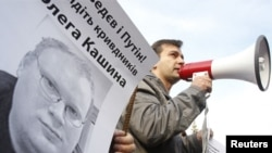 Ukrainian protesters hold a portrait of Russian journalist Oleg Kashin during a protest.