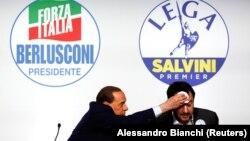برلوسکونی در حال پاک کردن عرق از پیشانی سالوینی، رهبر حزب لیگ