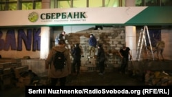 Ukrainian nationalists brick up a branch of the Russian-owned Sberbank in Kyiv on March 13.