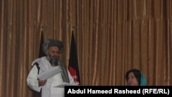 Afghan parliament members Hajji Abdul Basir (left) and Homa Soltani speak at a press conference where they showed the letter signed by Taliban leader Mullah Mohammad Omar on July 14.