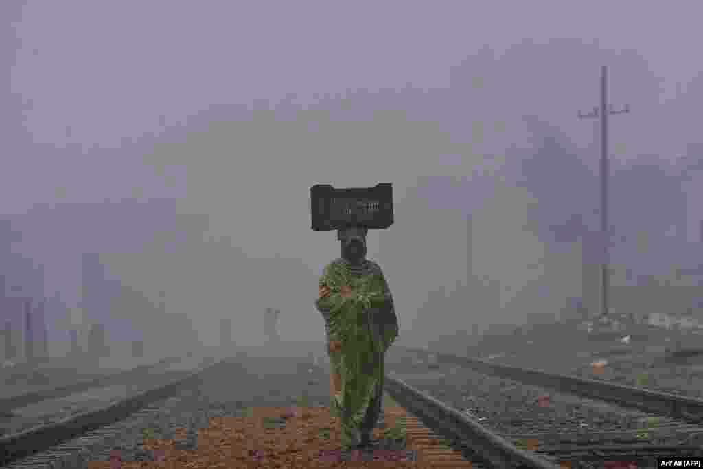A woman carries a basket on her head while walking on a railway track in thick smog and fog in Lahore, Pakistan. (AFP/Arif Ali)