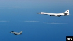 An RAF Typhoon fighter aircraft (left) flies close to a Russian strategic Tupolev TU-160 bomber in September 2015.