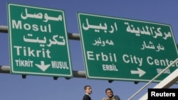 Workers add Turkoman language translations to traffic signs in multiethnic Kirkuk.