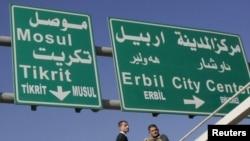 Workers add Turkoman language translations to traffic signs in multiethnic Kirkuk.