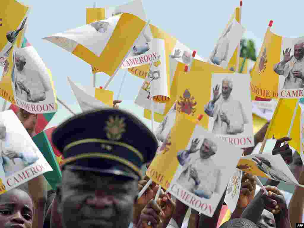 Schoolchildren wave flags showing Pope Benedict in Cameroon during his visit in March 2009.