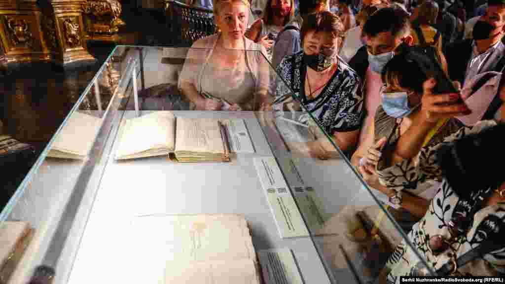 Відвідувачі розглядають експонати виставки у Софійському соборі