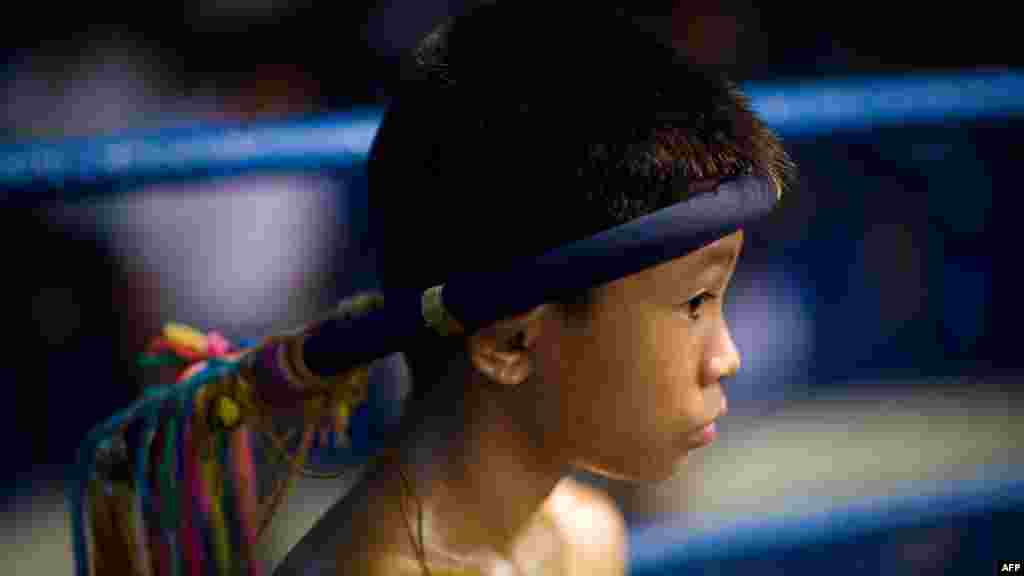 A child Muay Thai boxer focuses inside the ring ahead of his fight
