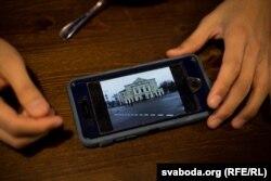 Цзыўай паказвае фота тэатру Янкі Купалы, які ён наведаў падчас вандроўкі ў Беларусь