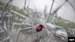 An ethnic Uyghur woman is seen through the broken window of a car dealership as cars damaged during the July unrest are visible in the background in a mainly Uyghur neighborhood in Urumqi.