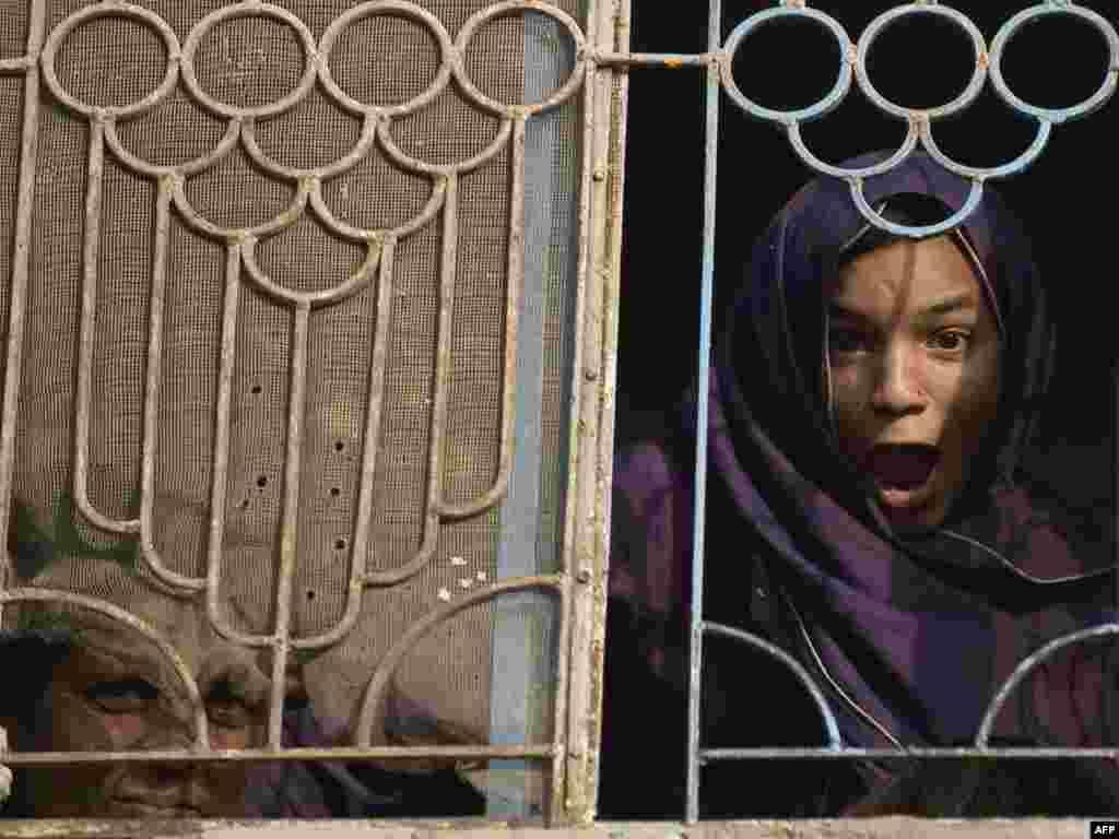 Pakistan -- A girl looks out of the window in Rawalpindi, 18Oct2009 - PAKISTAN, Rawalpindi : A Pakistani girl grimaces while looking out of a window in Rawalpindi, on the outskirts of capital Islamabad, on October 18, 2009. More than 100,000 people have fled South Waziristan, the lawless area on the Afghan border where Pakistan has launched a major ground assault against the Taliban.