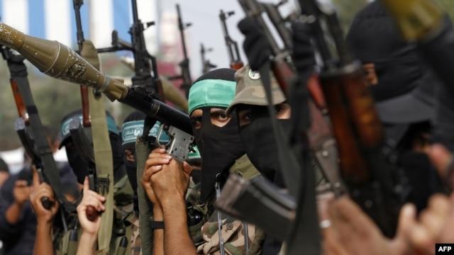 Membrii ai brigăzilor palestiniene Ezzedine al-Qassam serbează armistițiul drpt o victorie într-o tabără de refugiați din Fîșia Gaza