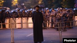 Armenia - An Armenian priest stands near rows of riot police on Marshal Bagramian Avenue, Yerevan, 28Jun2015.