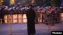 Armenia - An Armenian priest stands near rows of riot police on Marshal Bagramian Avenue, Yerevan, 28Jun2015.