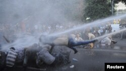 Armenia -- Protesters are hit by a jet of water released from a riot police vehicle during a rally against a recent decision to increase the tariff on electricity, in Yerevan, June 23, 2015.