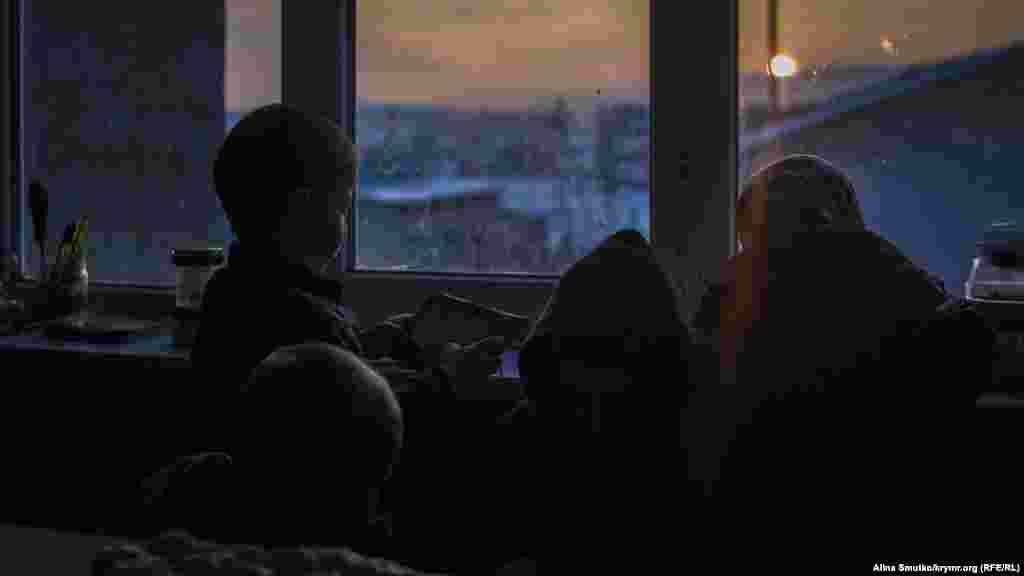 Дети Алиме и Теймура смотрят из окна на закат