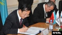 Sinopec Engineering компаниясының бас директоры Чжу Хайсин (сол жақта) және Атырау мұнай өңдеу заводының бас директоры Талғат Байтазиев шарт жасасып отыр. Атырау, 29 қазан 2009 жыл.