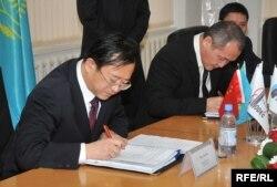 Sinopec Engineering компаниясының бас директоры Чжу Хайсин (сол жақта) мен Атырау мұнай өңдеу зауытының басшысы Талғат Байтазиев зауытты модернизациялау келісіміне қол қойып жатыр. Атырау, 29 қазан 2009 жыл.