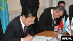 Генеральный директор компании Sinopec Engineering Чжу Хайсин (слева) и генеральный директор АНПЗ Талгат Байтазиев (справа) подписывают контракт на модернизацию завода. Атырау, 29 октября 2009 года.