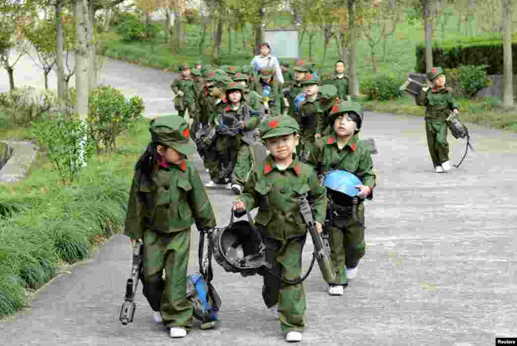 Chines kindergarten children dressed in military uniforms carry toy guns at a park in Dongyang, Zhejiang Province. (Reuters)