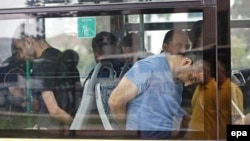 Turkish plainclothes policemen accompany soldiers, who have been detained following a failed coup attempt on July 15 , on a bus as they arrive at an Istanbul court on July 20.
