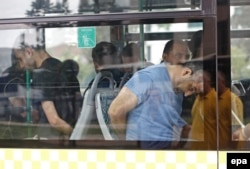 Turkish plainclothes policemen accompany detained soldiers following the failed coup attempt as they arrive at an Istanbul court July 20.