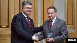 Президент України Петро Порошенко (ліворуч) вручає паспорт громадянина України Мішелю Терещенку. Київ, 21 березня 2015 року