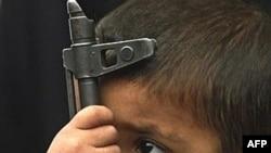 An Iraqi boy holds an AK-47 machine gun (file photo)