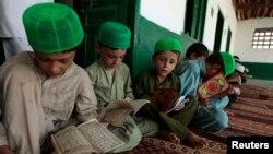 Дети изучают отрывки из Корана в медресе в Исламабаде. 21 августа 2013 года.
