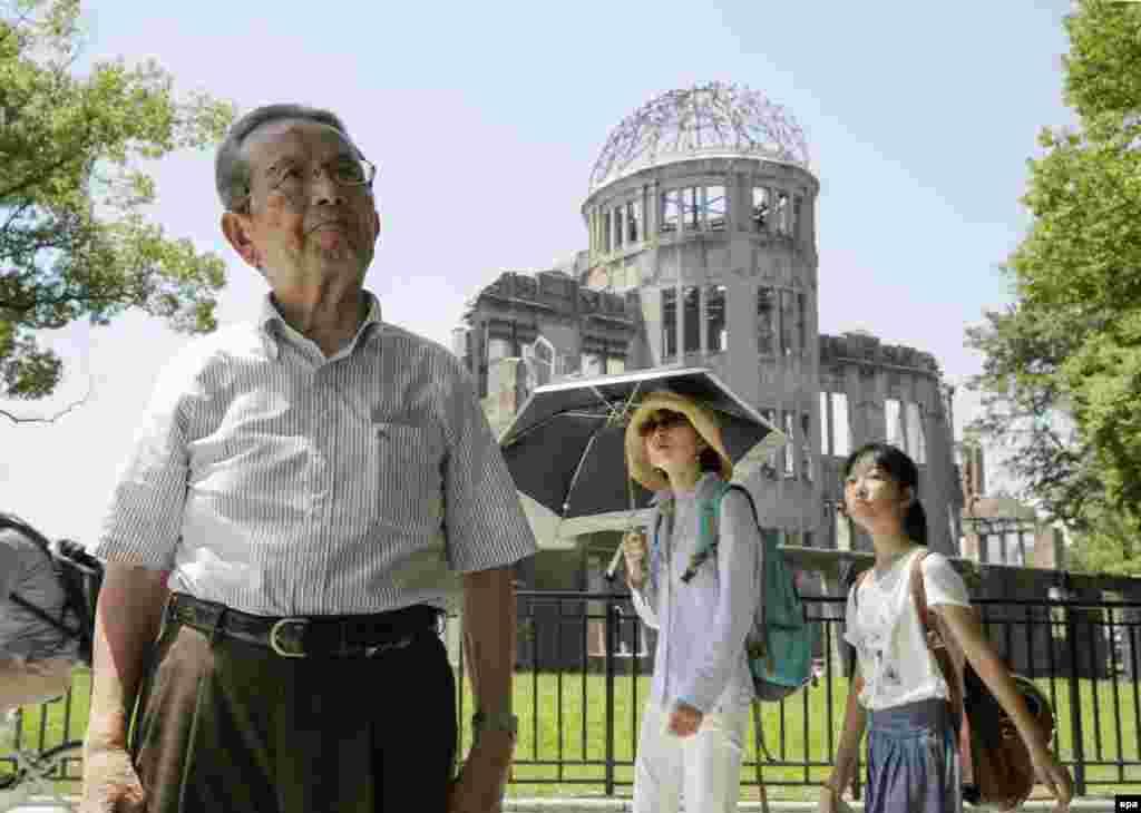 1 тамыз 2015 жыл. Хиросимаға тасталған атом бомбасы жарылысынан соң тірі қалған 82 жастағы Мицуо Кодама «Атом күмбезі» – соғысқа дейін Жапония сауда-өнеркәсіп палатасының көрме орталығы болған ғимараттың жанында тұр. Жарылыс эпицентрінен небары 160 метрде тұрған бұл ғимаратты атом бомбасы қатты бүлдіргенімен оның қабырғаларының бір бөлігі құламай қалған.